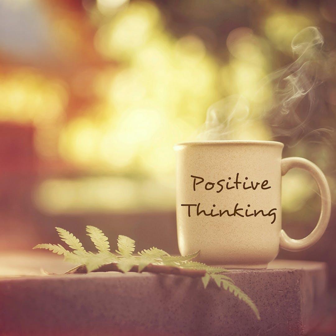 positive thinking mug on table with leaf