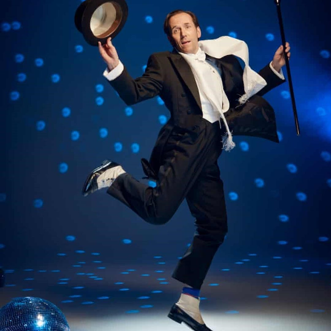 Ben Miller dancing in a cabaret style wearing black tie with a top hat and cane