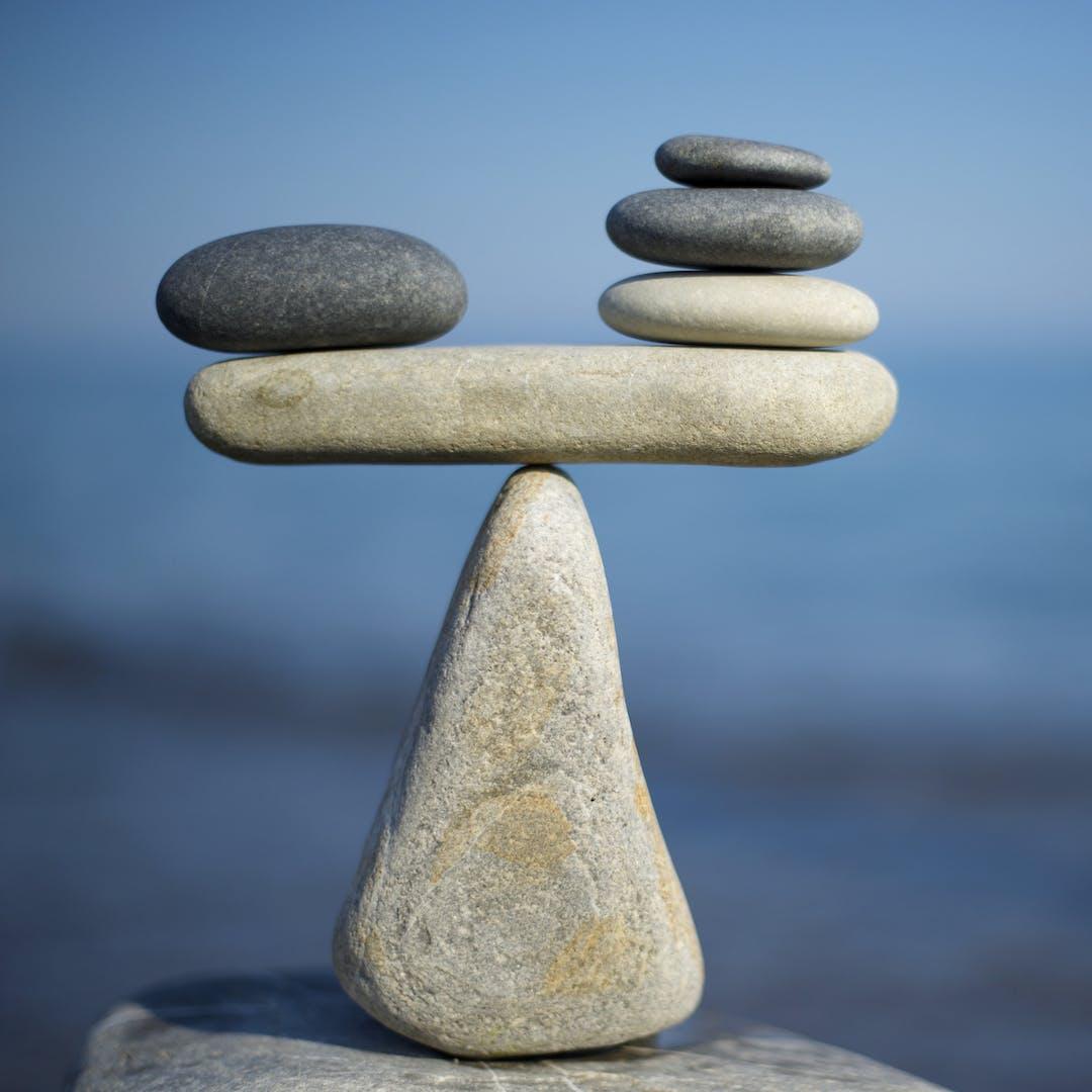 Pebbles balancing like scales on a triangular stone base