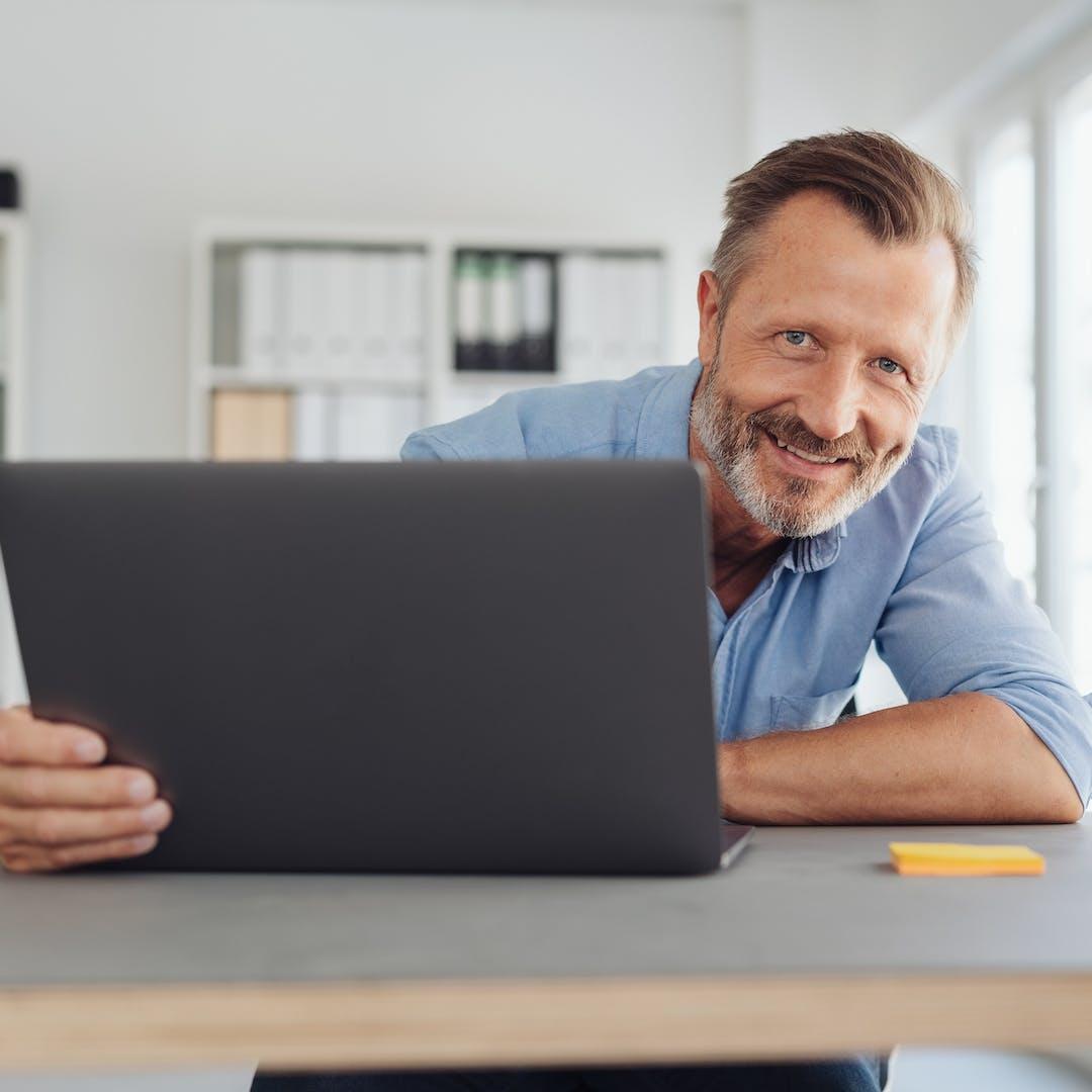 man smiling at camera with laptop