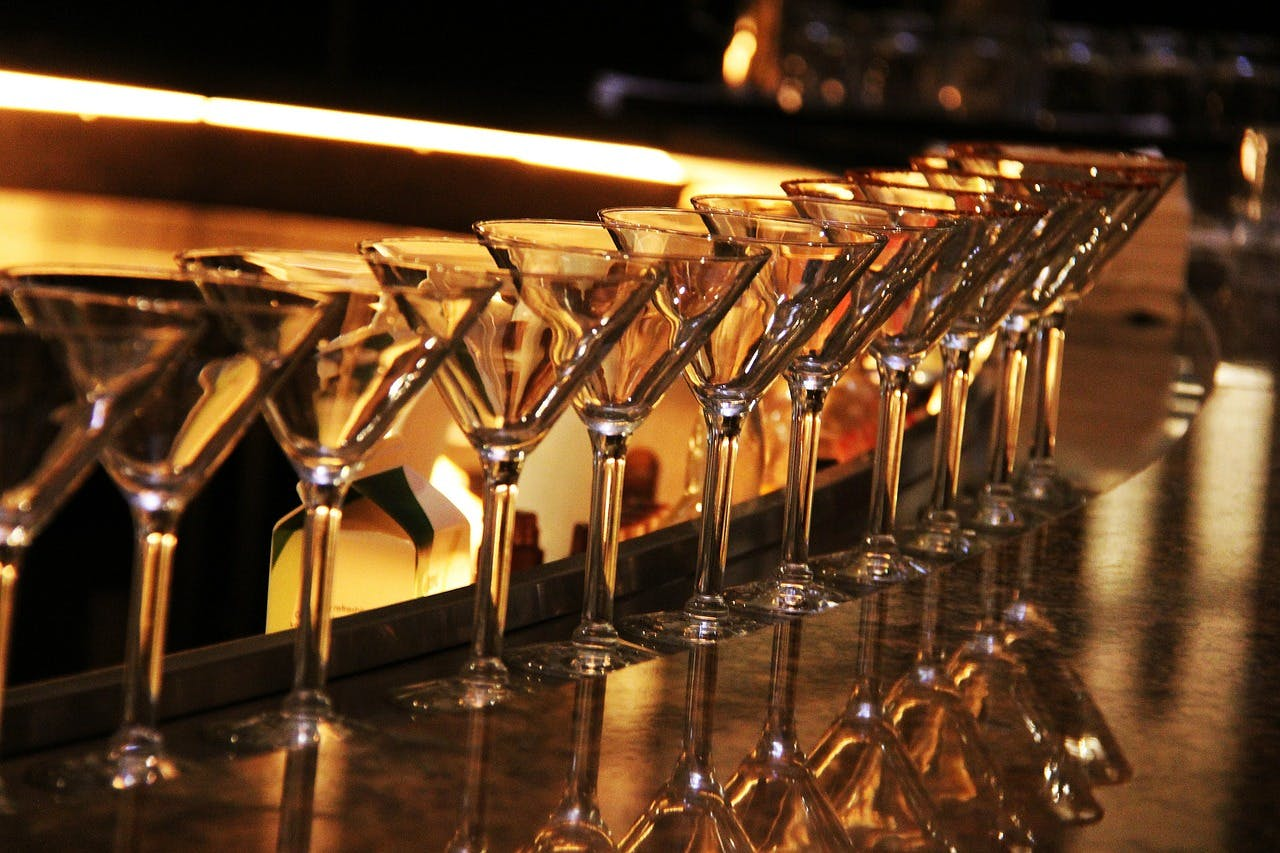 Glasses lined up in a dimly lit bar