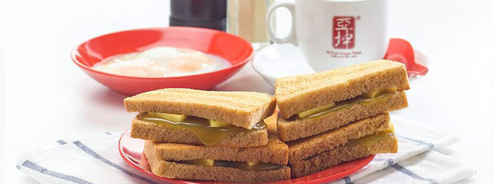 A bowl of two half-boiled eggs with black coffee and perfectly browned thin slices of bread, slathered in kaya and butter from Ya Kun Kaya Toast, close to 19 Nassim.