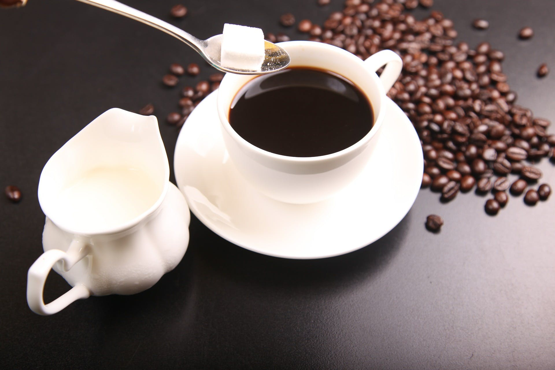 Cube of sugar being added to black coffee with a cup of milk on the side and coffee beans spread across the table