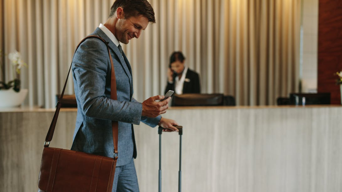 Man leaves the hotel with his luggage