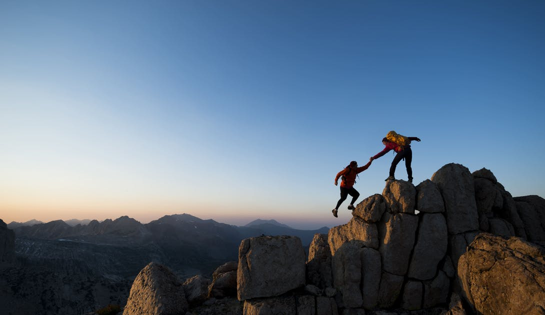 Climber helps another climber on a mountain