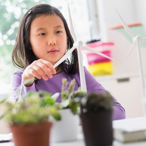 girl play with small wind turbine