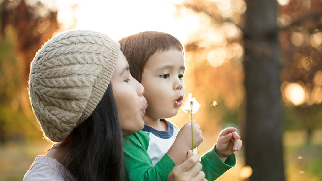 woman with boy breathe on a flower