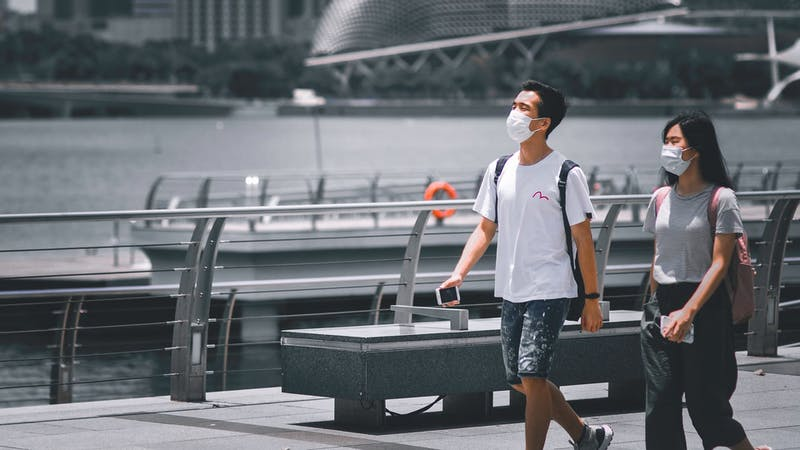 Jovens andando de máscara pela cidade Estudos Covid-19 Urbanos