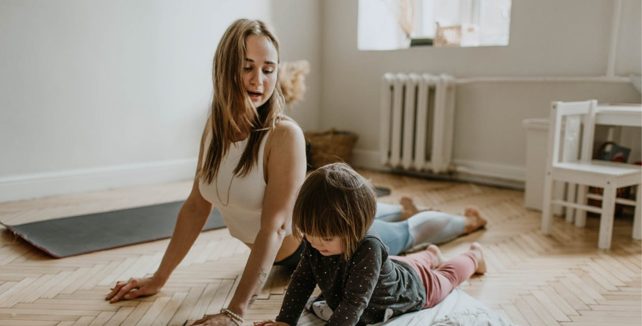 Woman and daughter exercising together at home