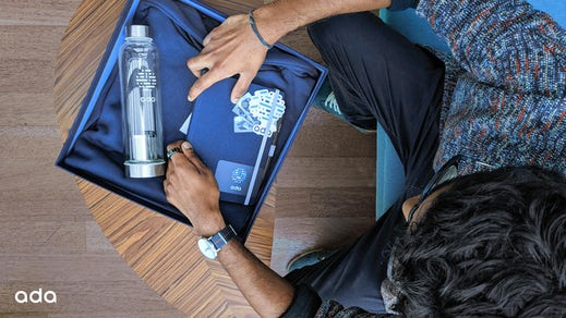 Photo shows Gobie unpacking a notepad, drink bottle, and stickers from his onboarding box.