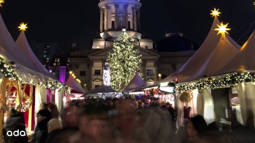 The Gendarmenmarkt Christmas market at night with lights and decorations.