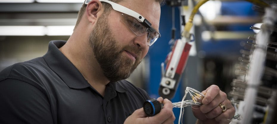 Boeing factory worker wearing Google glass while working on a wiring system