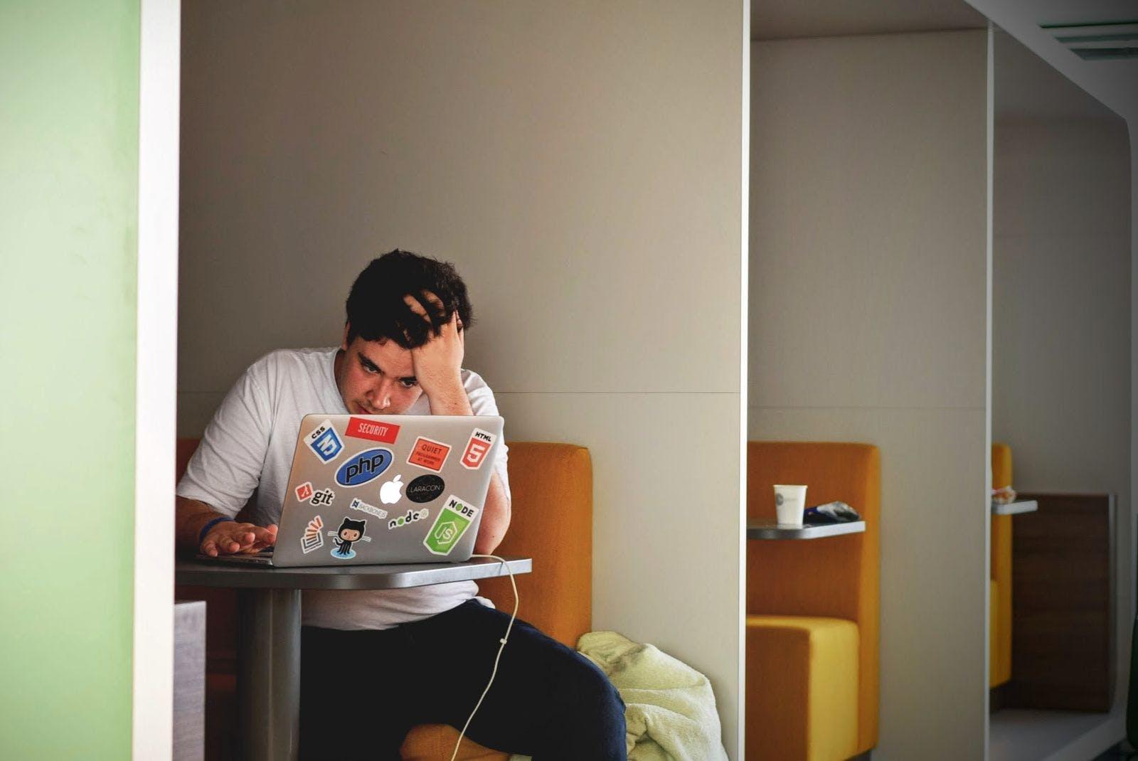 Foto de una persona abrumada trabajando en la computadora