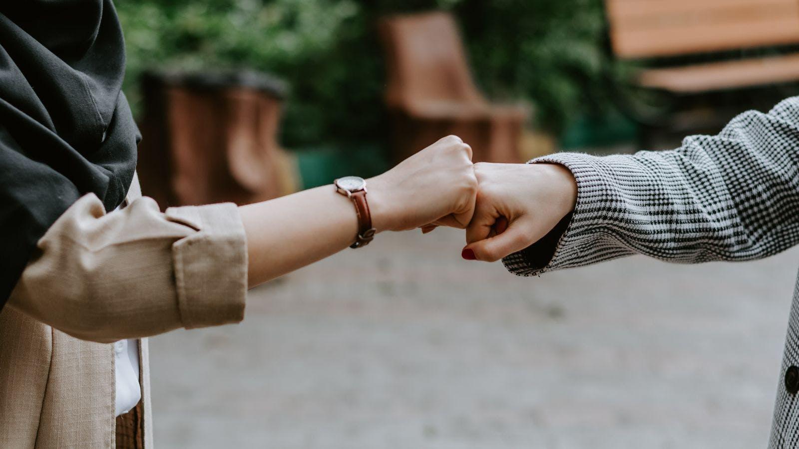 Foto de dos personas juntando puños