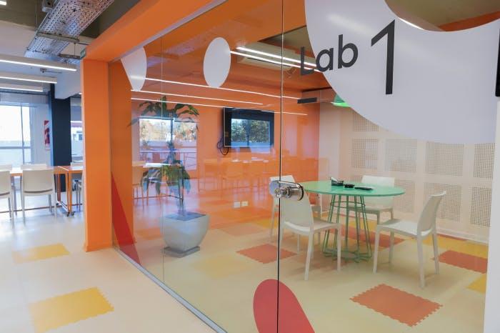 Foto de una parte de las oficinas de Aerolab donde se ve una sala con una mesa y sillas vacias