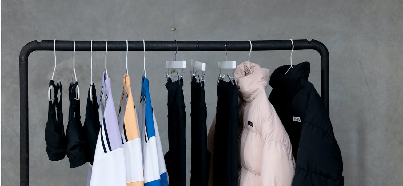 A rack of LSKD merchandise including tops, leggings, puffer jackets