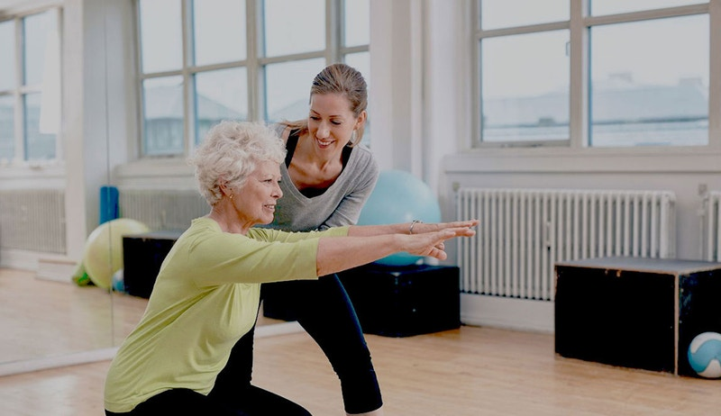Woman spotting an older lady who is doing an unweighted squat exercise