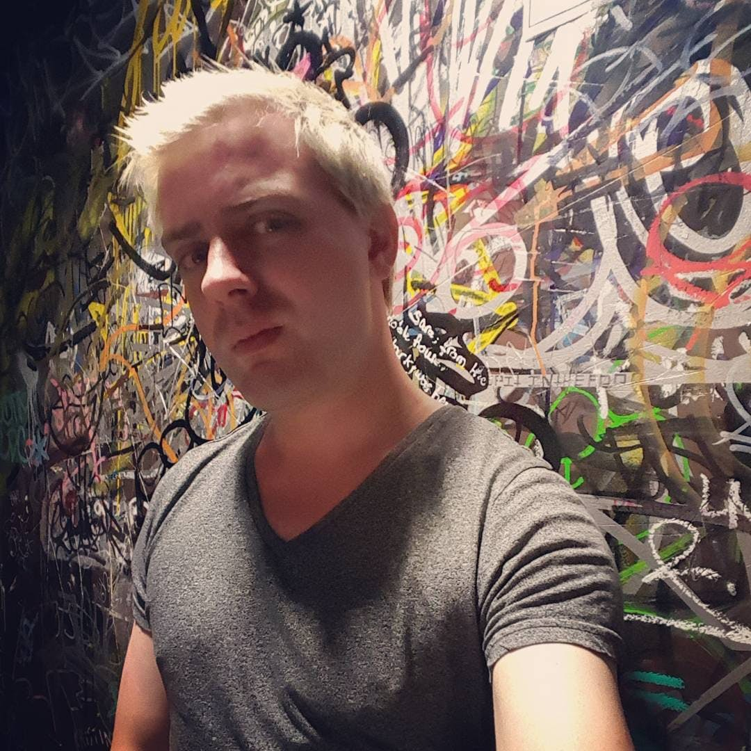 Medium shot photo of Alexis Watson, sporting their platinum blonde hair. A colorful wall of graffiti is in the background.