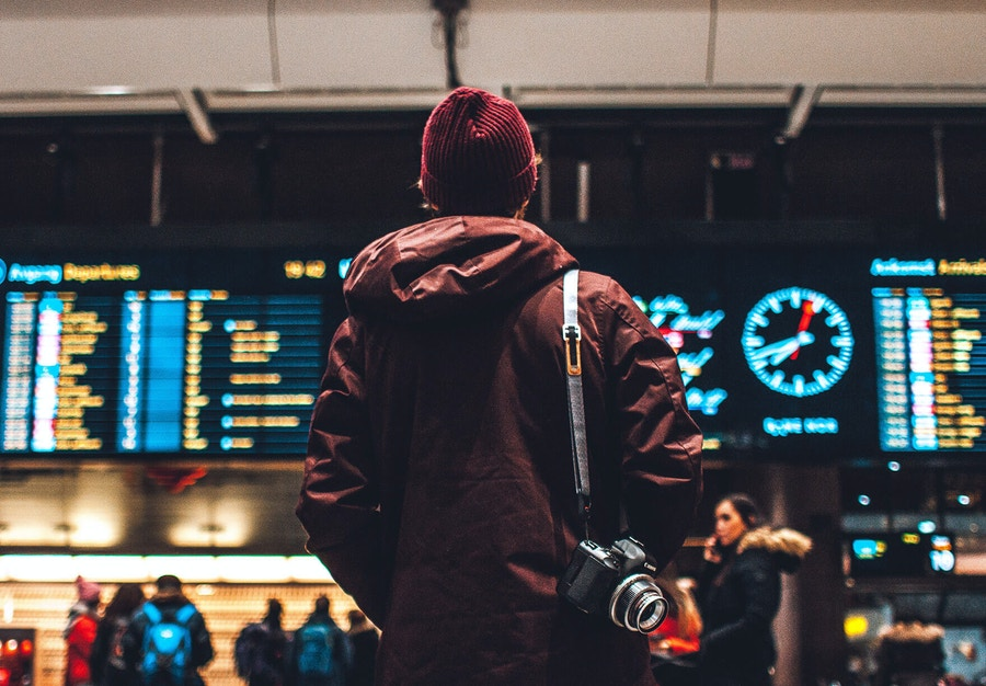 Man standing at an airport looking at signs