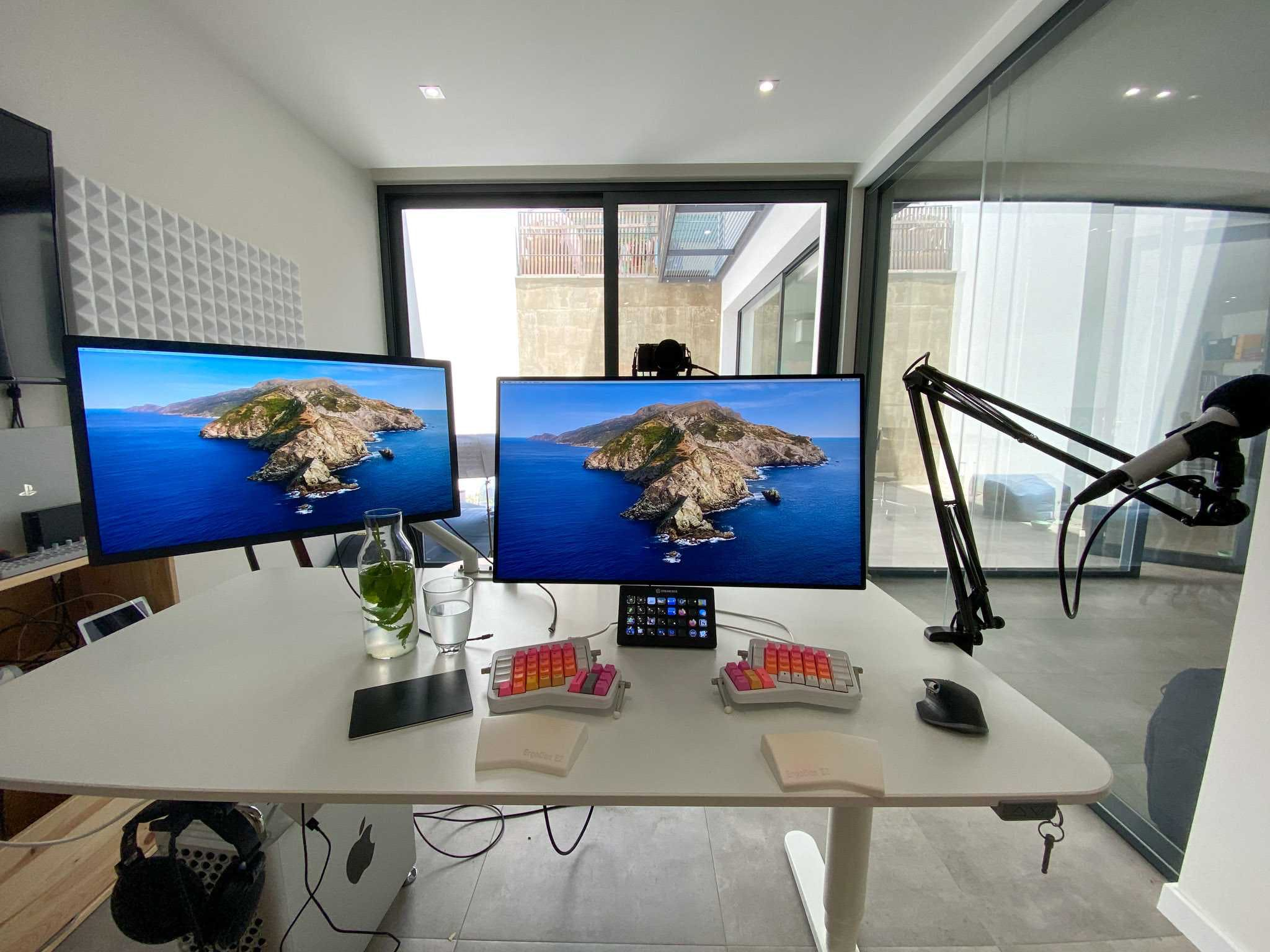 desk with keyboard, mouse, two monitors and microphone