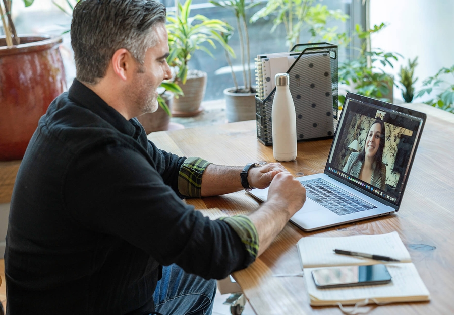 Remote video call interview between a smiling independent contractor and a hiring manager on laptop screen