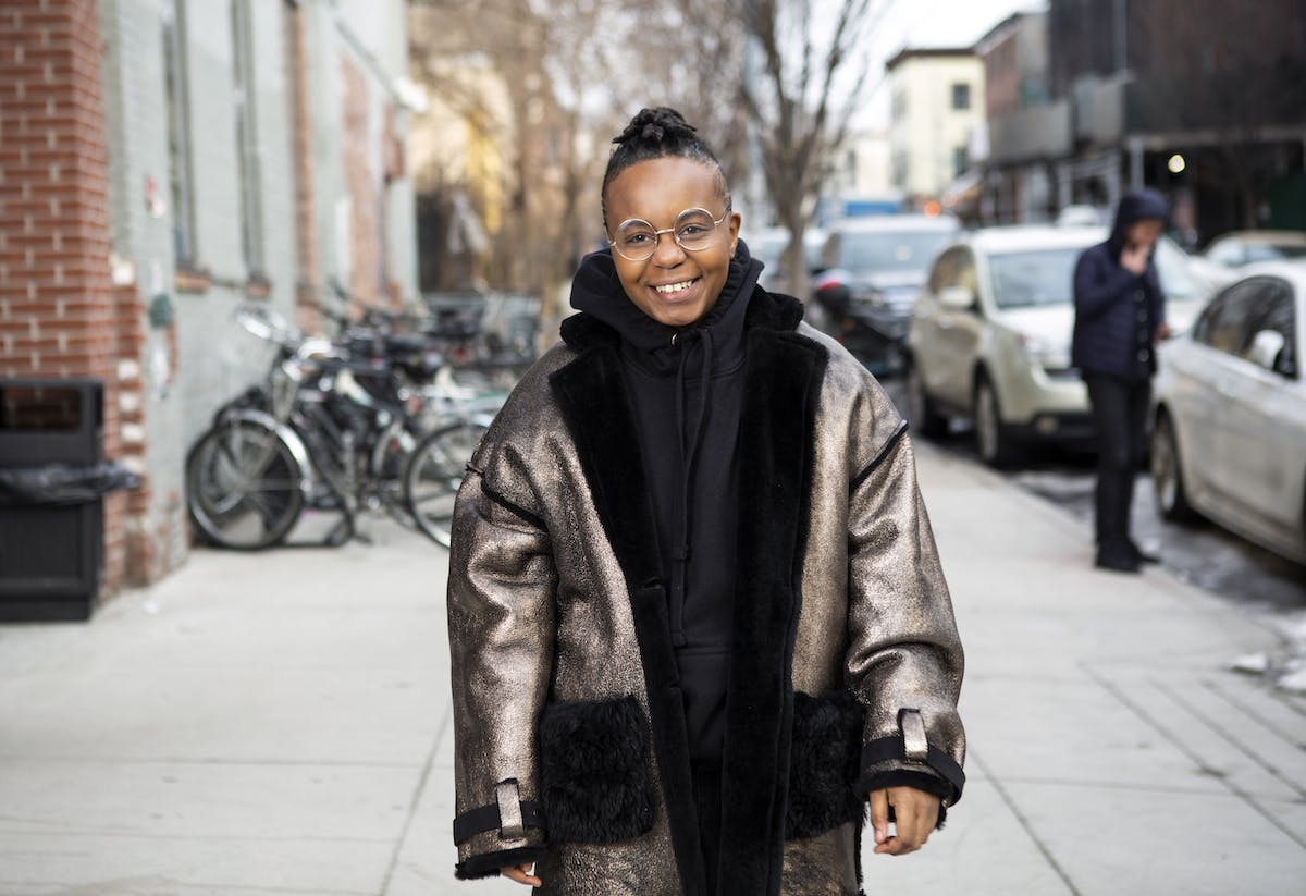 A transmasculine person in a winter coat on the sidewalk