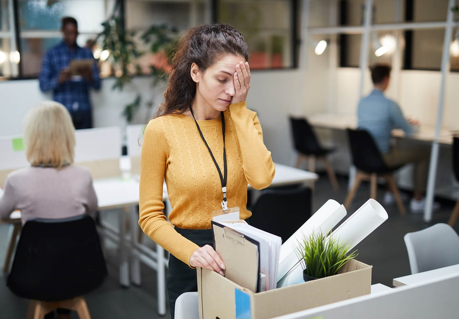 Woman in a pink sweater looking unhappy in an office