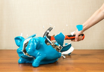 piggy bank being smashed with a hammer