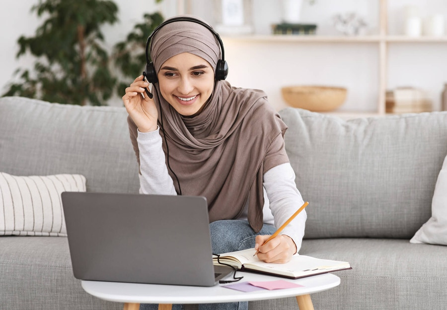 A woman wearing hijab working happily on her laptop