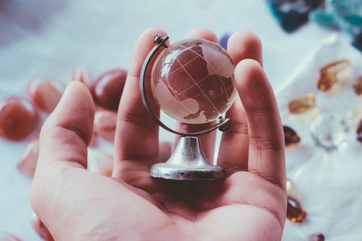 hand holding a small glass globe