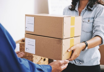 A person delivering boxes to someone with outstretched arms