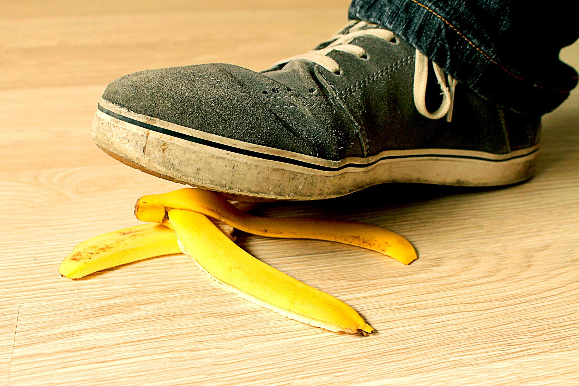 black shoe stepping on banana peel