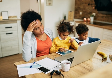 woman working with two children playing nearby