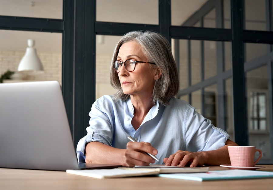 An older woman pensively fills out a form