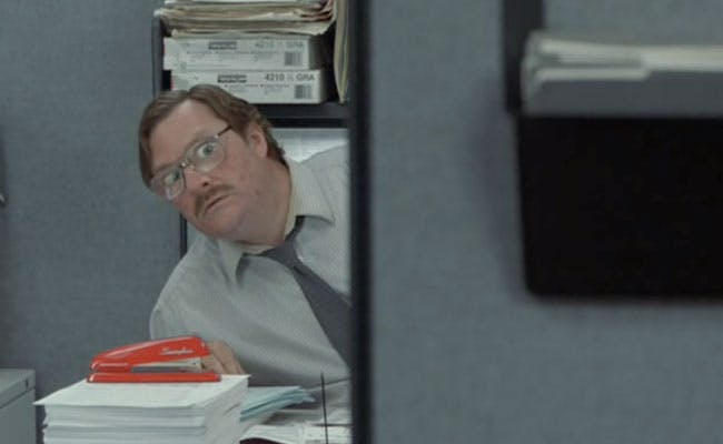 Milton from Office Space sitting with his stapler
