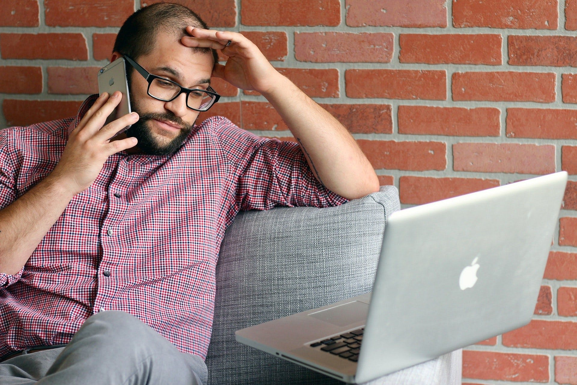 Man looking annoyed talking on the phone next to his laptop