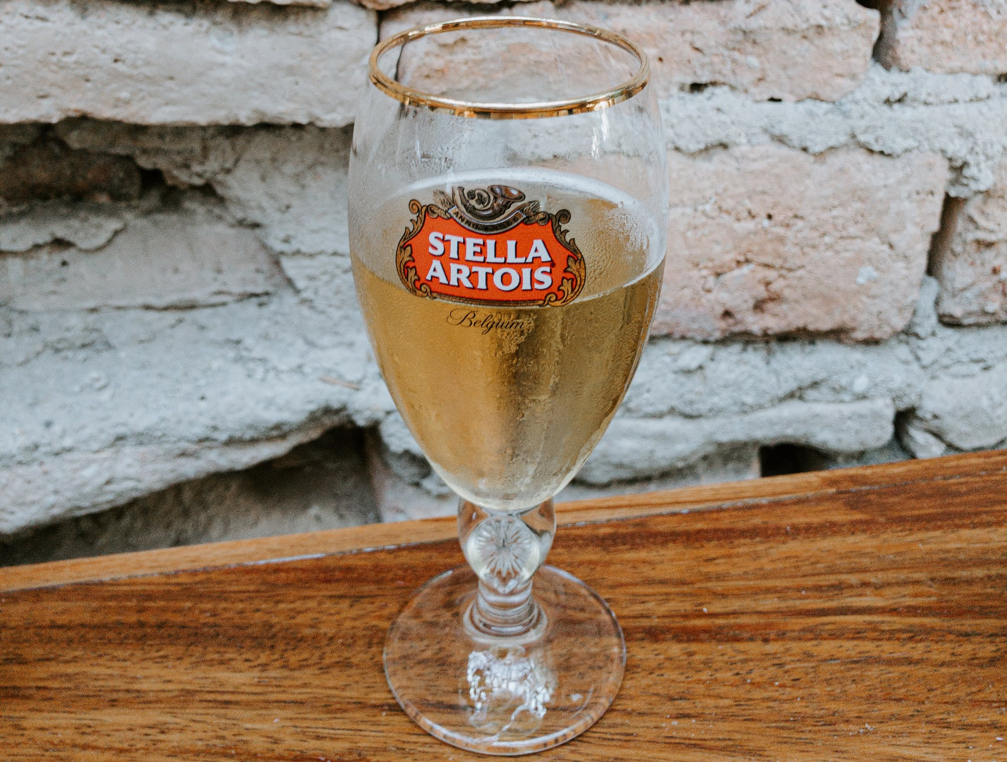 Glass of Stella Artois on table next to brick wall