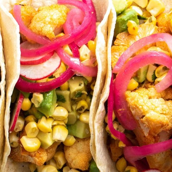 Four vegan tacos filled with sweetcorn, avocado and onion