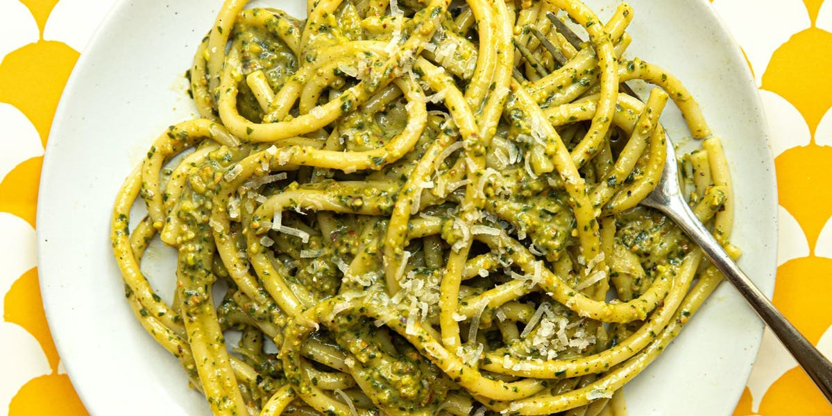 pesto pasta on white plate and yellow/white background