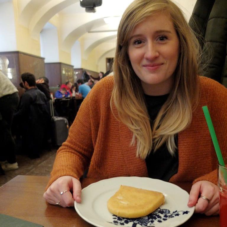 Woman holding plate with piece of fried cheese the size of a slice of bread
