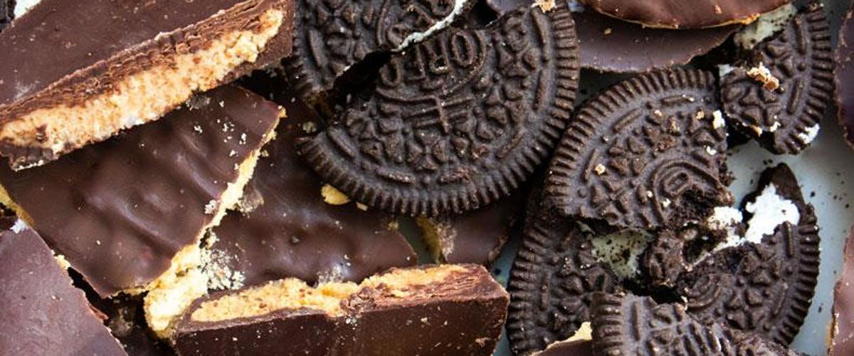 Close up image of broken oreos, chocolate digestives, and peanut butter cups.