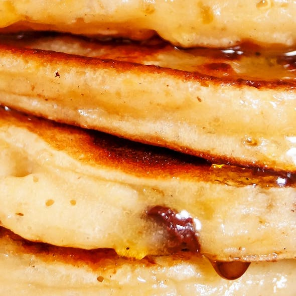 close up pancake stack with dripping syrup