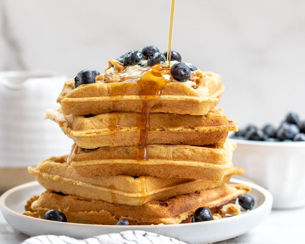large stack of waffles with blueberries and syrup on