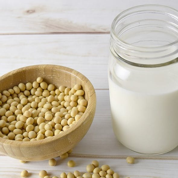Bowl of raw soy beans and glass of soy milk