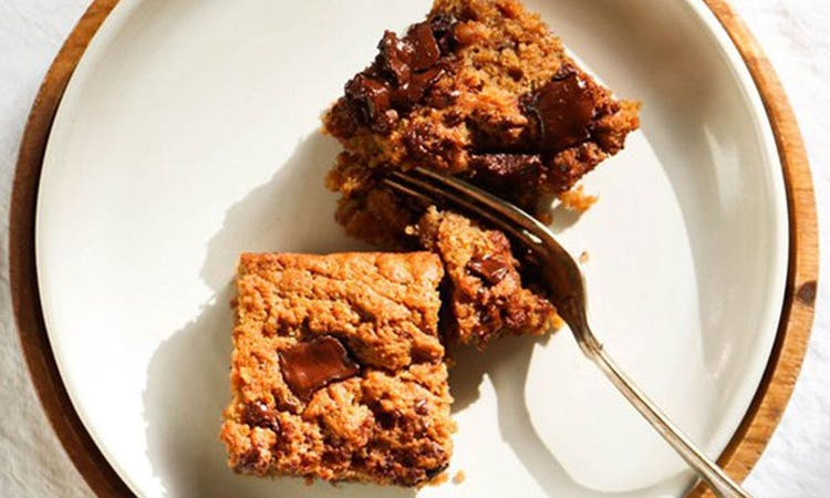 Birdseye image of two squares of blondie on a white plate. A fork lays on its side cutting through the upper piece of blondie.