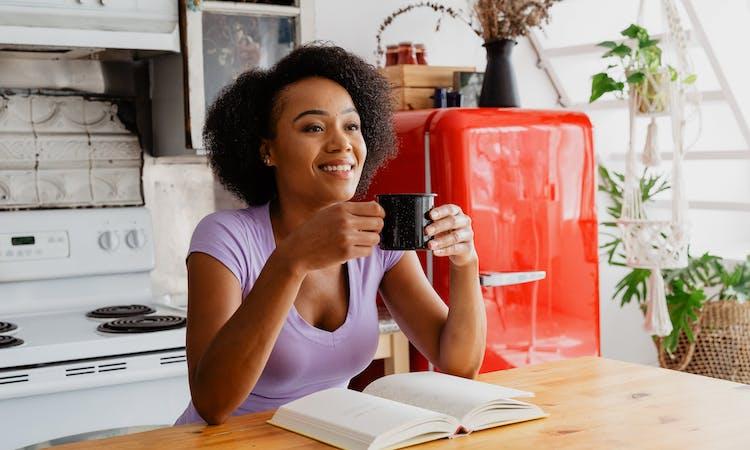 woman enjoying coffee in kitchen