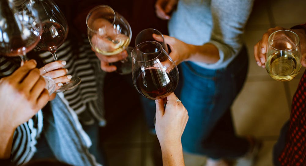 Image of hands holding wine glasses, taken from above - you can't see any faces. There's a mix of white and red wine in the six glasses you can see.