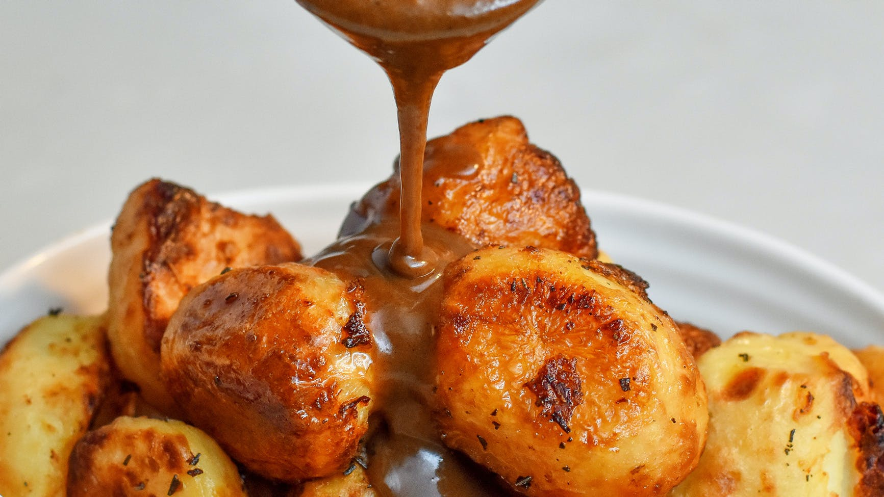 gravy being pourned over roast potatoes