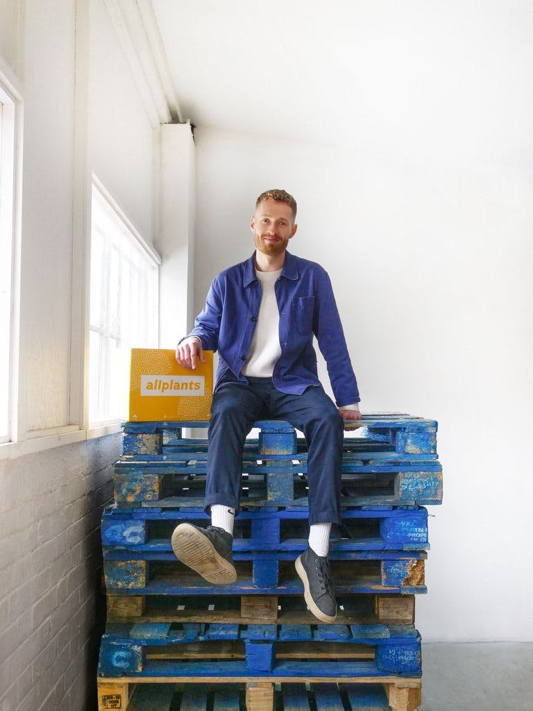 Image of our director of customer experience, Ferdie, sat on top of a stack of blue palettes wearing slack trousers, a white t-shirt, and an unbuttoned blue shirt. He's smiling with his right arm resting on top of an allplants delivery box.