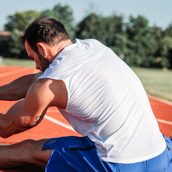 man stretching on an athletic track
